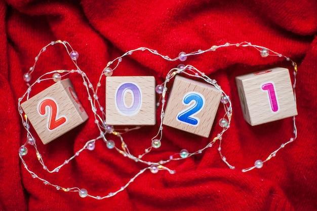Numéros 2021 à partir de cubes pour enfants sur fond rouge vif. nouvel an noël