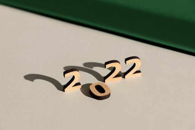 Numéros 2022 avec de longues ombres dures sur un fond gris et vert foncé