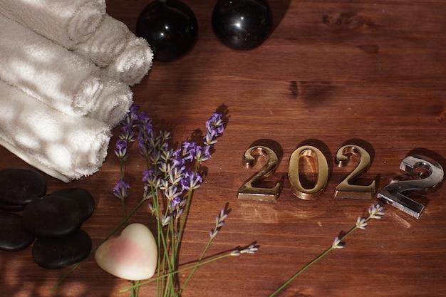 Numéros 2022 sur la table à côté de lavande, pierres de massage chaudes et serviettes.