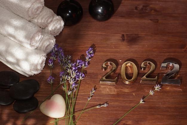 Numéros 2022 sur la table à côté de pierres de massage chaudes et de serviettes.