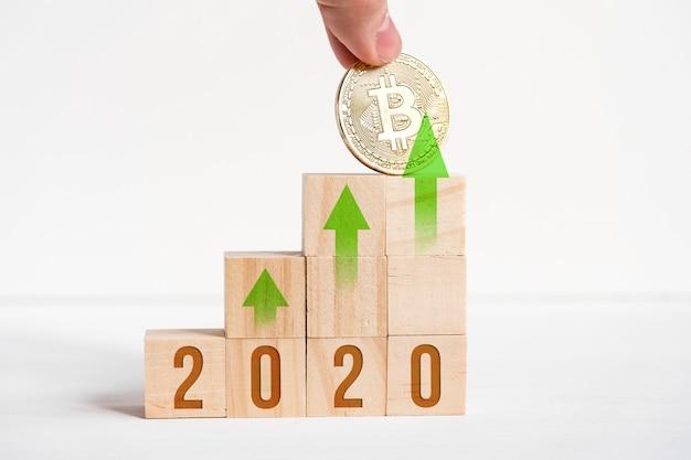 Numéros sur des cubes en bois sur un fond blanc à côté d'une pièce de monnaie bitcoin.
