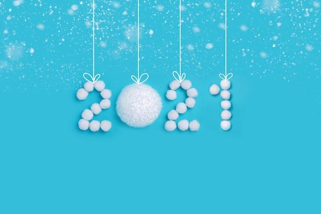 Numéros du nouvel an 2021 en neige artificielle blanche et boules sur fond bleu