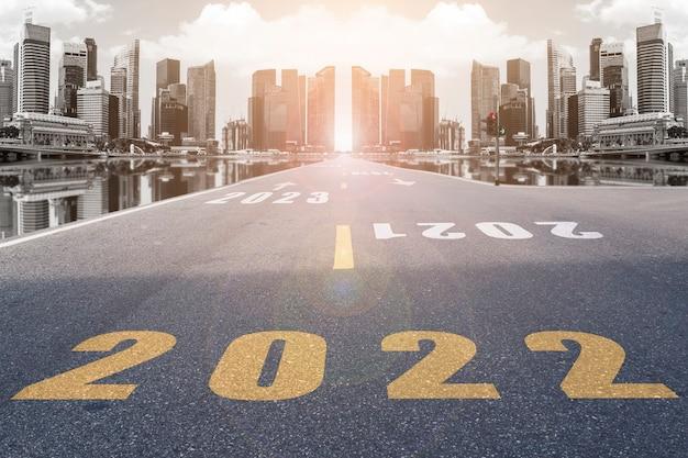 Numéros du symbole 2022 dans la rue menant aux gratte-ciel de la ville au soleil du soir. utiliser pour les concepts du nouvel an et se diriger vers le succès.