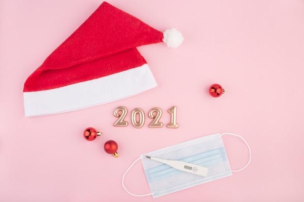 Numéros de nouvel an sur fond rose, masques médicaux et thermomètre, vue du dessus