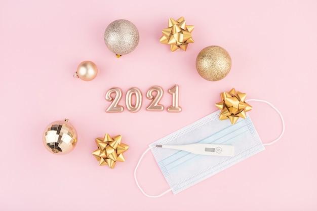 Numéros de nouvel an sur fond rose, vue de dessus, masques médicaux et thermomètre