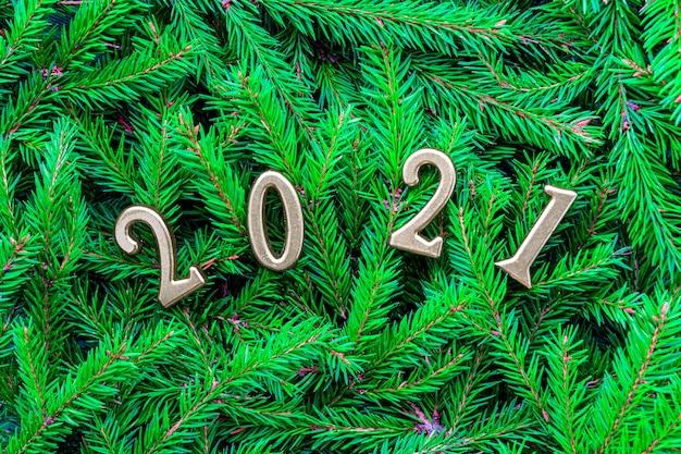 Numéros d'or 2021 sur fond de branches d'arbres de noël. concept de vacances nouvel an et noël
