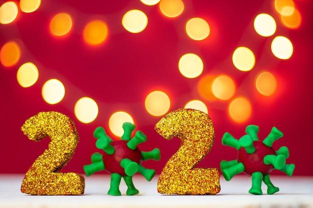 Numéros scintillants dorés 2020 avec virus covid-19 avec bokeh sur fond rouge. copiez l'espace.