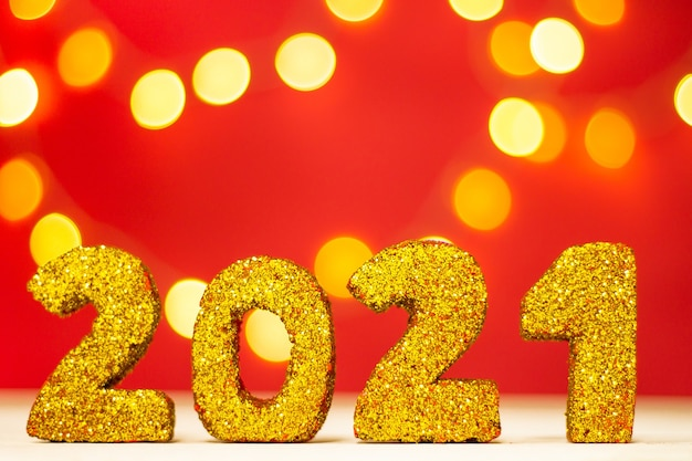 Numéros scintillants dorés 2021 avec bokeh sur fond rouge. joyeux noël et bonne année. copiez l'espace.