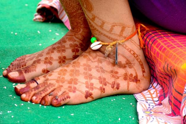 Nuptiale indienne pakistanaise montrant la conception de mehndi de pied sur la cérémonie de mariage