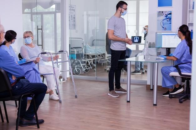 Nusre avec visière contre le coronavirus et jeune patient parlant dans la zone de réception vérifiant les rendez-vous...