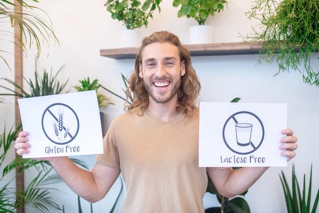 Nutrition adéquat. joyeux jeune homme barbu en t-shirt tenant montrant des affiches sans lactose sans gluten debout à l'intérieur