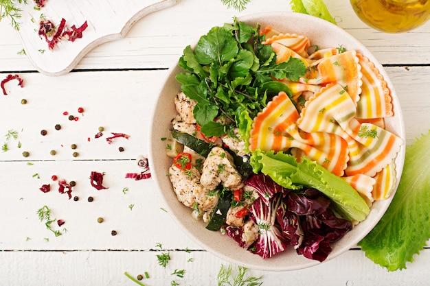 Nutrition adéquat. salade diététique. farfalle pâtes blé dur avec filet de poulet au four avec aubergine, courgettes et salade dans un bol. vue de dessus. mise à plat