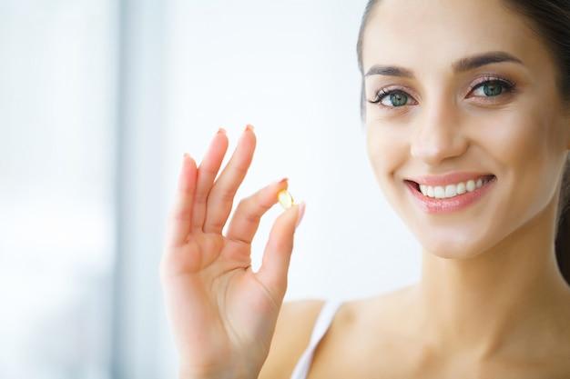 Nutrition. mode de vie sain. femme tenant une pilule avec de l'huile de poisson oméga-3. suppléments, vitamines.