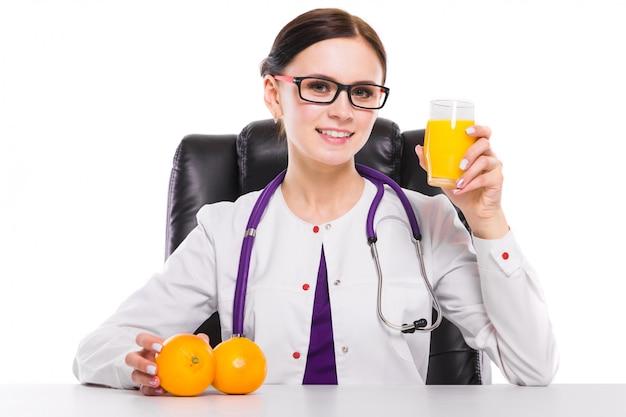 Nutritionniste assis dans son lieu de travail, montrant et offrant un verre de jus d'orange tenant orange à la main, sur fond blanc