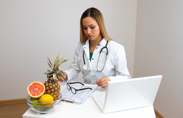 Nutritionniste femelle avec fruits travaillant à son bureau