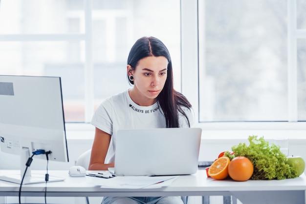 Nutritionniste féminine en blouse blanche assise à l'intérieur du bureau sur le lieu de travail avec ordinateur portable.
