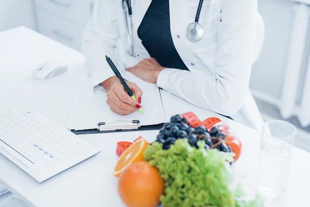 Nutritionniste féminine en blouse blanche assise à l'intérieur du bureau sur le lieu de travail.
