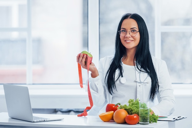 Nutritionniste féminine en blouse blanche tenant une pomme avec un ruban à mesurer.