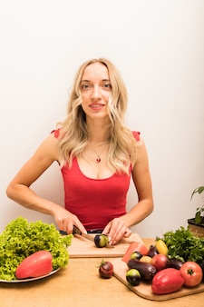 La nutritionniste de fille s'assied à une table avec des légumes