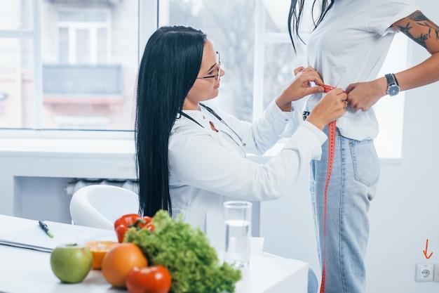 Nutritionniste mesurant la taille du patient par ruban adhésif à l'intérieur du bureau.