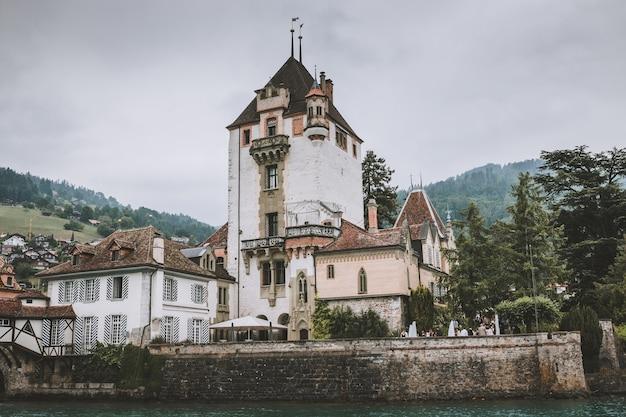 Oberhofen, suisse - 22 juin 2017 : vue sur le château d'oberhofen - musée vivant et parc du navire, suisse, europe. paysage d'été, temps nuageux, ciel dramatique et journée ensoleillée. imprimer la photo