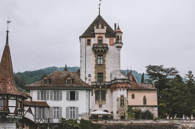 Oberhofen, suisse - 22 juin 2017 : vue sur le château d'oberhofen - musée vivant et parc du navire, suisse, europe. paysage d'été, temps nuageux, ciel dramatique et journée ensoleillée