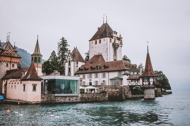 Oberhofen, suisse - 24 juin 2017 : vue sur le château d'oberhofen - musée vivant et parc du navire, suisse, europe. paysage d'été, temps ensoleillé, ciel bleu et journée ensoleillée