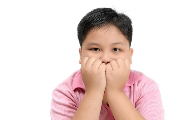 Obèse gros garçon se ronger les ongles isolé