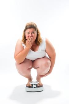Obèse jeune femme accroupie sur une échelle