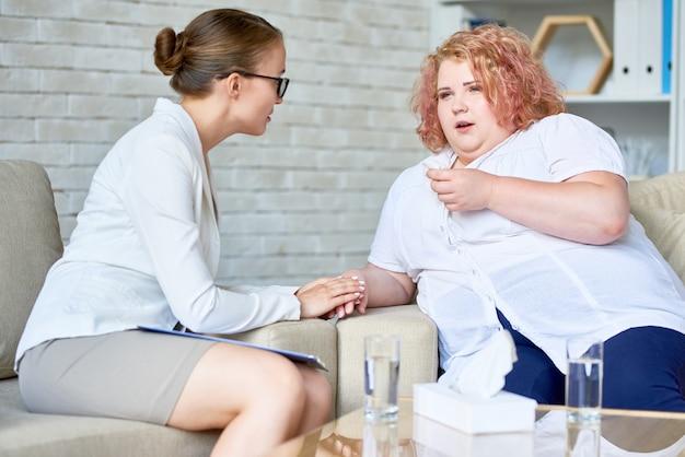 Obèse jeune femme discutant de dépression avec un psychiatre
