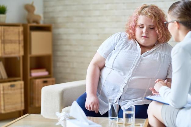 Obèse jeune femme parlant à un psychiatre