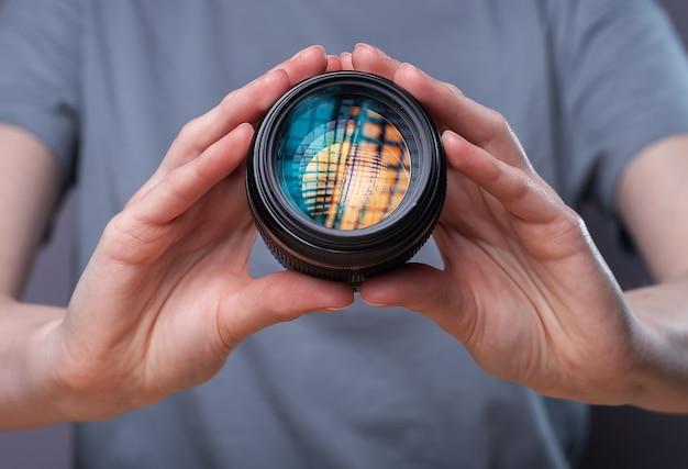Objectif d'appareil photo numérique avec une belle softbox de studio se reflétant dans les mains d'une femme photographe.