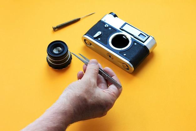 Objectif de la caméra vintage et des outils, des pincettes et un tournevis avec du papier jaune, réparation de la caméra