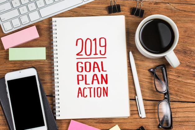 Objectif du nouvel an 2019, plan, texte d'action sur le bloc-notes avec des accessoires de bureau.