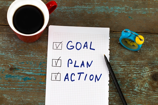 Objectif du nouvel an, plan, action - texte sur le bloc-notes avec une tasse de café. motivation commerciale, concepts d'inspiration.