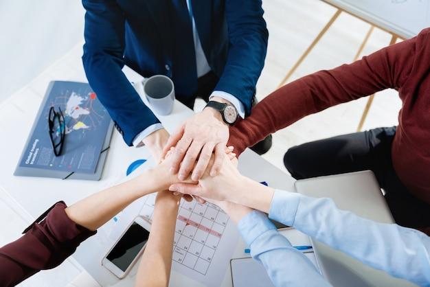 Objectif de l'équipe. vue de dessus des jeunes mains féminines et masculines se tiennent au-dessus de la table où se trouvent des documents et des verres