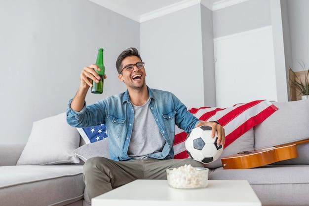 Objectif! homme regardant un match de football à la télévision à la maison.