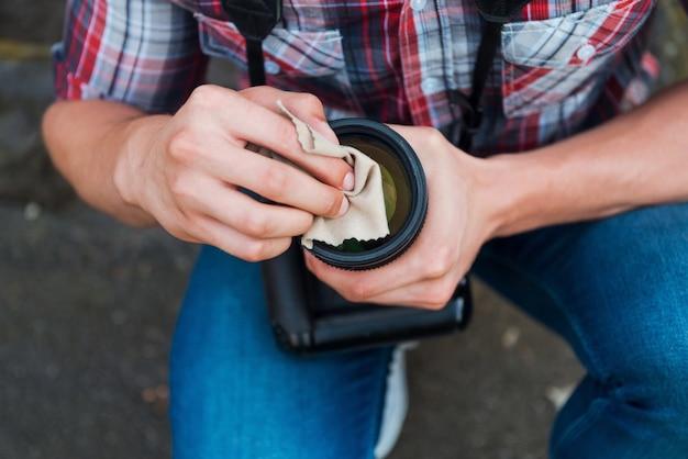 Objectif de nettoyage de photographe. gros plan d'un homme nettoyant l'objectif de son appareil photo numérique en se tenant debout à l'extérieur