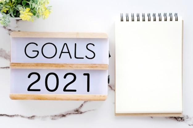 Objectifs 2021 sur boîte en bois et papier cahier vierge sur marbre blanc