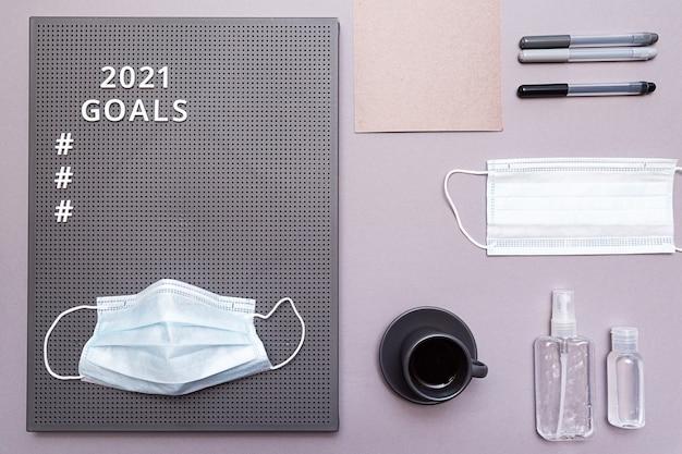 Objectifs 2021 avec masque de protection pour le visage, bouteilles de désinfectant pour les mains et tasse à expresso