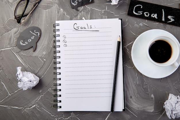 Objectifs comme mémo sur un cahier avec idée, papier froissé, tasse de café