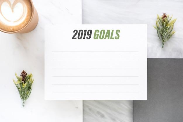 Objectifs du nouvel an 2019 sur une carte en papier blanc et une tasse à café sur un bureau