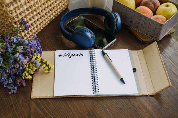 Objectifs de résolutions du nouvel an phrase de motivation dans un cahier ouvert sur la table nature morte en plein air