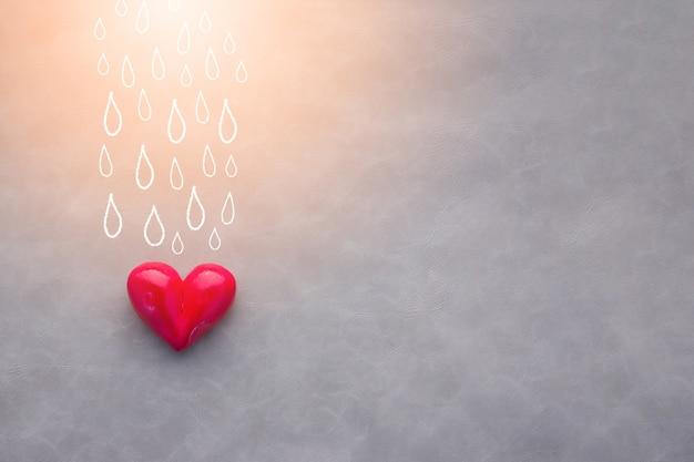 Objet coeur rouge avec dessin d'eau pleuvoir sur fond gris