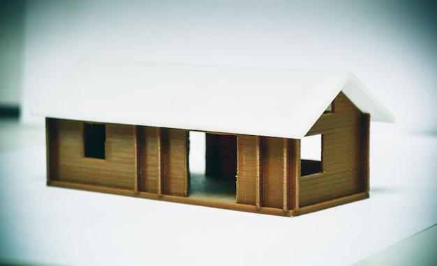 Objet coloré lumineux imprimé par imprimante 3d. isolé sur fond blanc. l'imprimante 3d tridimensionnelle automatique effectue la modélisation des couleurs vertes en plastique en laboratoire. maison marron blanc.