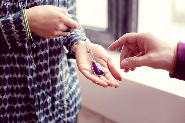 Objet magique. gros plan d'une puissante amulette magique étant en main féminine