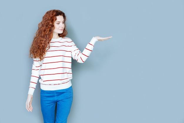 Objet virtuel. smart agréable jeune femme debout sur fond bleu et regardant sa main tout en tenant un objet virtuel en elle