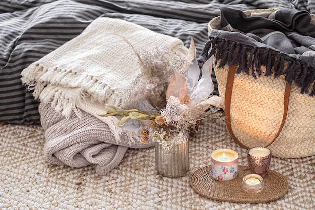 Objets décoratifs dans un intérieur confortable avec grand sac en paille en osier et éléments décoratifs pour la maison.
