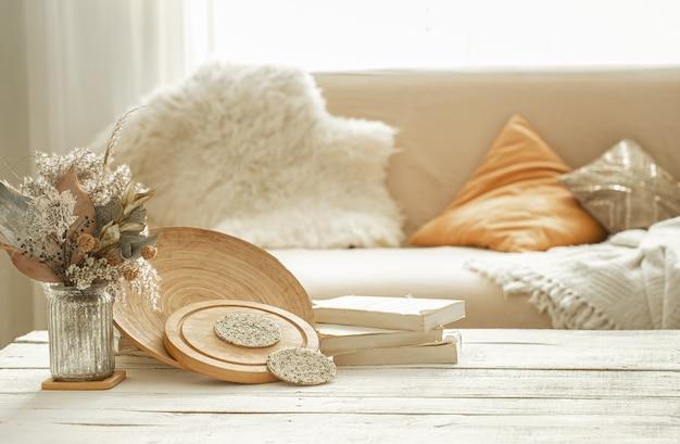 Objets de décoration dans l'intérieur confortable de la pièce, un vase avec des fleurs séchées sur une table en bois clair.