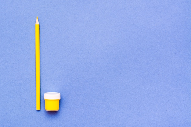 Objets de dessin au crayon jaune et gouache jaune sur fond bleu